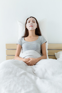 Woman lying down on bed and do maskingの写真素材 [FYI00743882]