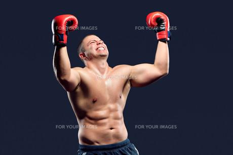 Portrait of a boxer champion enjoying his victory. Studio shot.の写真素材 [FYI00744583]