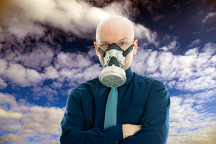 businessman with gas mask in front of cloudy skyの写真素材 [FYI00745517]