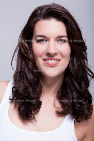 young attractive woman with dark hair in portrait laughingの写真素材 [FYI00745849]