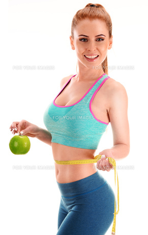 Young woman holding measure tape and apple. Weight lossの写真素材 [FYI00746070]