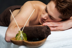 Young man relaxing on massage tableの写真素材 [FYI00746295]