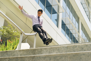 Chinese Businessman Going Downstairs Sliding On Rail For Joyの写真素材 [FYI00746703]