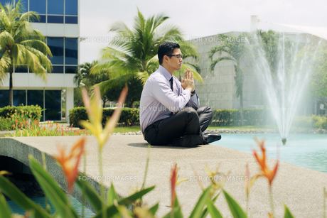 Chinese Business Man Meditate Yoga Outside Office Buildingの写真素材 [FYI00746704]