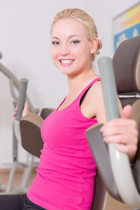 young woman does sports exercises in a gymの写真素材 [FYI00747722]