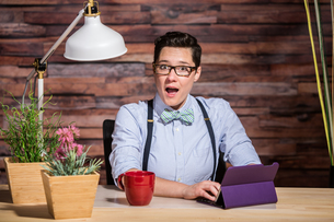 Excited Woman at Desk with Tabletの写真素材 [FYI00748222]
