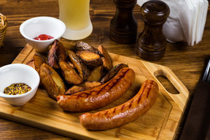 Grilled sausages with roast potato with spicesの写真素材 [FYI00748405]