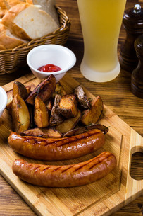 Grilled sausages with roast potato with spicesの写真素材 [FYI00748406]