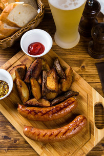 Grilled sausages with roast potato with spicesの写真素材 [FYI00748412]