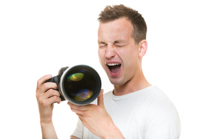 Young pro photographer with digital camera - DSLR and a huge telephoto lens in his well equiped studio, taking photos - getting really tired from all the hard work(color toned image  shallow DOF)の写真素材 [FYI00749097]