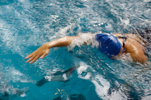 Female swimmer in an indoor swimming pool - doing crawl (shallow DOF)の写真素材 [FYI00749113]