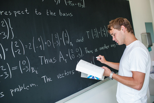 Handsome college student solving a math problem during math class in front of the blackboard/chalkboard (color toned image)の写真素材 [FYI00749123]