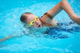 Young girl in goggles and cap swimming crawl stroke style in the blue water poolの写真素材 [FYI00749128]