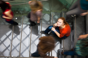 At the university/college - Students rushing up and down a busy stairway - confident pretty young female student looking upwards while listening to music on her mp3 player (color toned image)の写真素材 [FYI00749137]