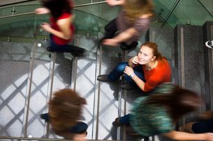 At the university/college - Students rushing up and down a busy stairway - confident pretty young female student looking upwards while listening to music on her mp3 player (color toned image)の写真素材 [FYI00749138]