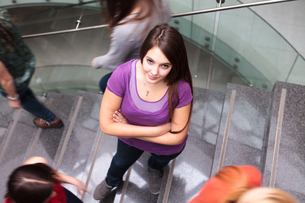 At the university/college - Students rushing up and down a busy stairway - confident pretty young female student looking upwards while listening to music on her mp3 player (color toned image)の写真素材 [FYI00749140]