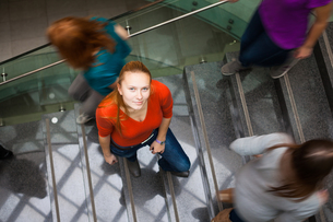 At the university/college - Students rushing up and down a busy stairway - confident pretty young female student looking upwards while listening to music on her mp3 player (color toned image)の写真素材 [FYI00749143]