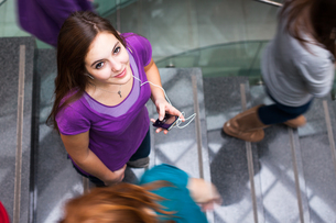At the university/college - Students rushing up and down a busy stairway - confident pretty young female student looking upwards while listening to music on her mp3 player (color toned image)の写真素材 [FYI00749144]