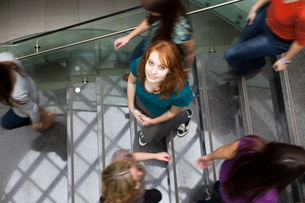 At the university/college - Students rushing up and down a busy stairway - confident pretty young female student looking upwards while listening to music on her mp3 player (color toned image)の写真素材 [FYI00749145]