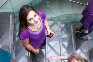 At the university/college - Students rushing up and down a busy stairway - confident pretty young female student looking upwards while listening to music on her mp3 player (color toned image)の写真素材 [FYI00749154]