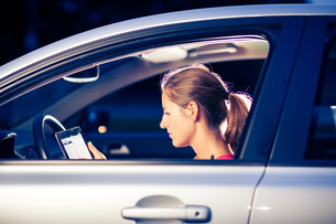 Pretty, female driver using her tablet computer (shallow DOF  color toned image)の写真素材 [FYI00749161]