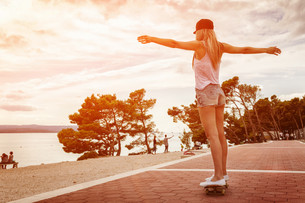 Young carefree woman riding a skateboard along the coastの写真素材 [FYI00749792]
