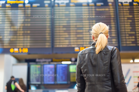 Female traveller checking flight departures board.の素材 [FYI00749951]