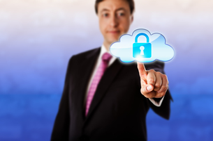 Smiling Businessman Touching A Locked Cloud Iconの写真素材 [FYI00750176]