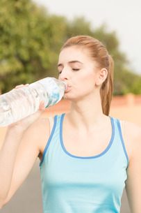 young woman doing sports and drinking waterの写真素材 [FYI00750369]