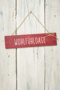 red wooden sign in front of a white wooden wall - oasisの素材 [FYI00750696]