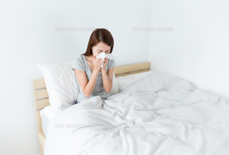 Woman sneeze on the bedの素材 [FYI00751313]