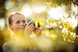 Pretty female amateur photographer taking photos outdoors, doing what she loves to doの写真素材 [FYI00752160]
