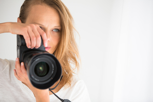 Pretty, female photographer with digital camera - DSLR and a huge telephoto lensの写真素材 [FYI00752161]
