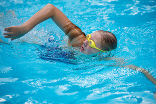 Young girl in goggles and cap swimming crawl stroke style in the blue water poolの写真素材 [FYI00752163]