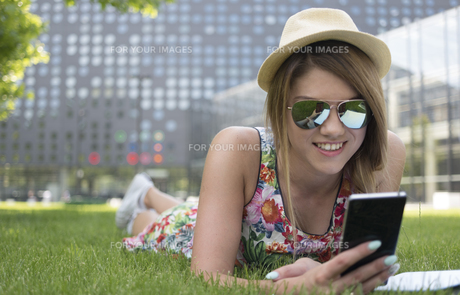 Pretty Girl Using her Phone While Lying on Grassesの素材 [FYI00752240]