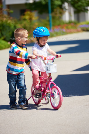 Boy and girl in park learning to ride a bikeの写真素材 [FYI00752633]