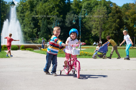 Boy and girl in park learning to ride a bikeの写真素材 [FYI00752656]