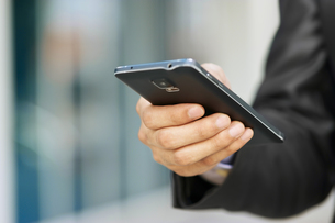 Business Man Holding Phablet Smartphone And Watching E-mailの写真素材 [FYI00752760]