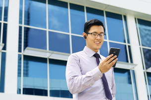 Businessman Talking Video Call On Mobile With Bluetooth Headsetの写真素材 [FYI00752770]