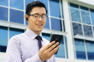 Businessman Talking Video Call On Mobile With Bluetooth Handsfreeの写真素材 [FYI00752774]