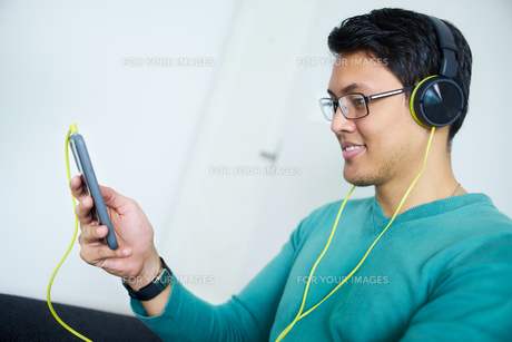 Chinese Man With Green Headphones Listens Podcast Phone At Homeの写真素材 [FYI00752775]