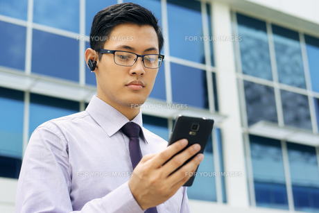 Businessman Talking Video Call On Mobile With Bluetooth Headsetの写真素材 [FYI00752780]