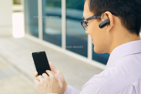 Businessman Calling On Mobile Phone With Bluetooth Headsetの写真素材 [FYI00752782]