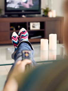 Woman Relax On Sofa Watching Film On TV With Remoteの写真素材 [FYI00752784]