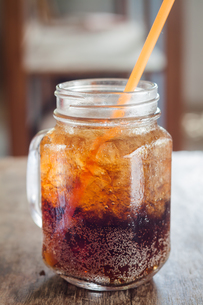 Glass of cola with ice on wooden tableの写真素材 [FYI00753714]