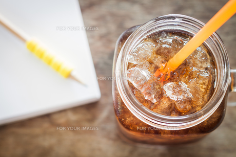 Glass of cola with ice on wooden tableの写真素材 [FYI00753719]