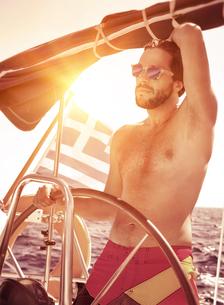 Handsome guy driving sailboatの写真素材 [FYI00753969]