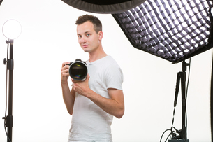 Young pro photographer with digital camera - DSLR and a huge telephoto lens in her well equiped studio, taking photos (color toned image  shallow DOF)の写真素材 [FYI00754005]