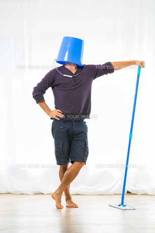 Young man mopping the floor. Or is he?の写真素材 [FYI00754006]