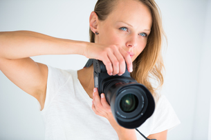 Pretty, female photographer with digital camera - DSLR and a huge telephoto lensの写真素材 [FYI00754017]